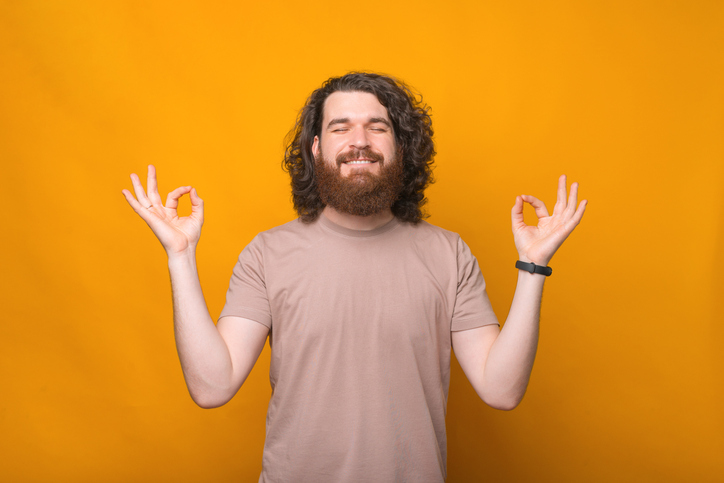 Portrait of young bearded hipster man making zen gesture over yellow background