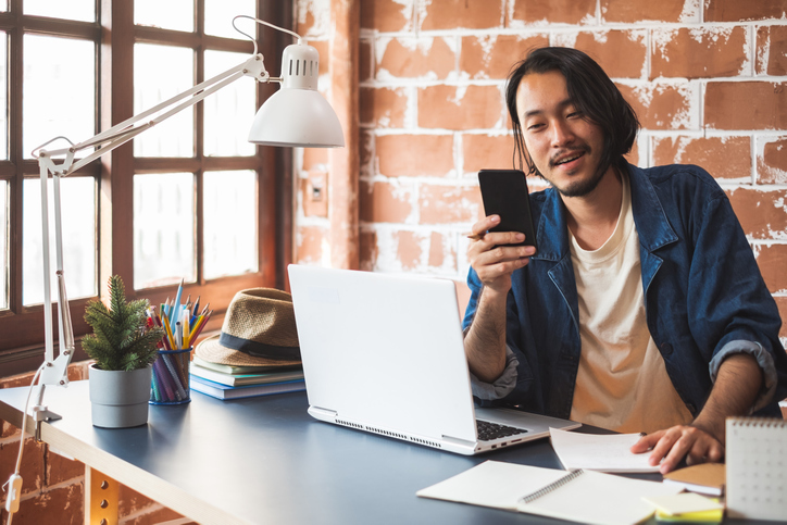 Young Asian man using phone and working on laptop for business creative designer.